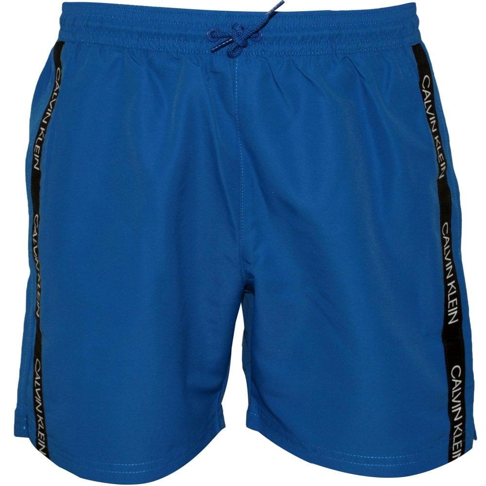 7cbde75e80 Calvin Klein Logo Tape Boys Swim Shorts, Imperial Blue | UnderU